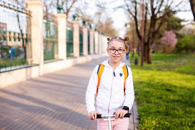大都市の中心部の暖かい緑豊かな公園で白いスクーターでスケートを学ぶ面白いブロンドの女の子。夏のアクティビティ