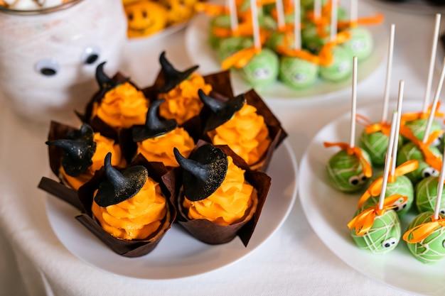 ハロウィーンのお祝いのためにキャンディーバーにオレンジ色のクリームと甘い黒い帽子のカップケーキ