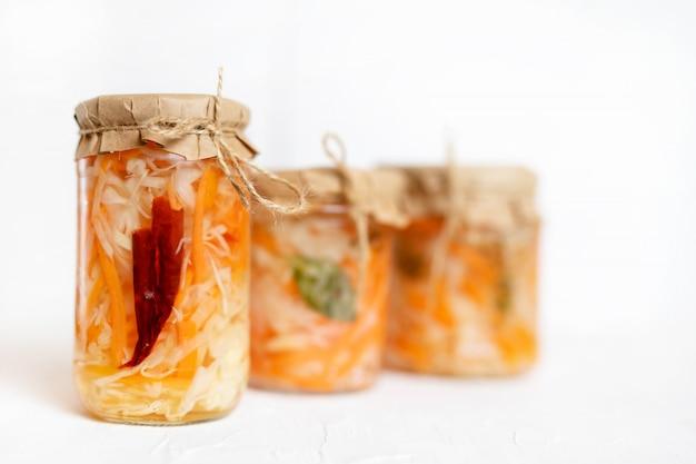 Три банки квашеной капусты и моркови в собственном соку со специями, белый деревянный стол. традиционный домашний