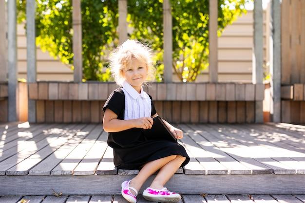 Счастливая маленькая школьница с обедом, книгой и карандашами. снова в школу на открытом воздухе