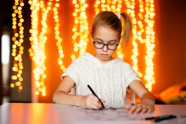 サンタクロースを描く大きな黒い眼鏡のブロンドの女の子。クリスマスと新年のテーマ、黄色のボケ