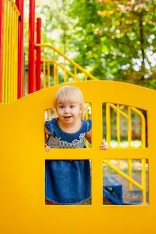 屋外の遊び場で遊ぶ子供。小さな女の赤ちゃんは学校や幼稚園の庭で遊ぶ