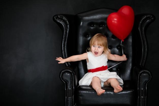 バレンタインの日に赤いハート形風船で肘掛け椅子に座っている小さなブロンドの女の子