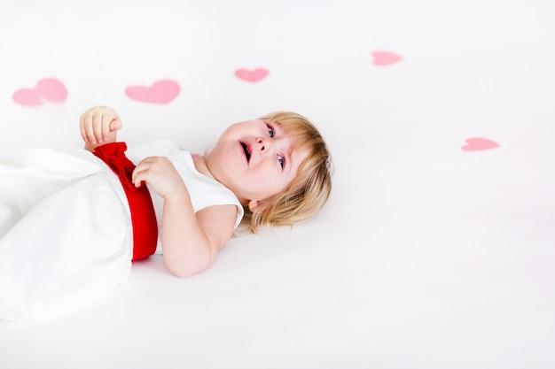 バレンタインの日にピンクの心と白い床に赤いリボンと白いドレスの小さなブロンドの女の子