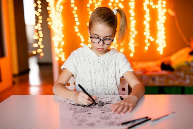 Очаровательная маленькая девочка пишет письмо санта-клаусу, сидящему на столе
