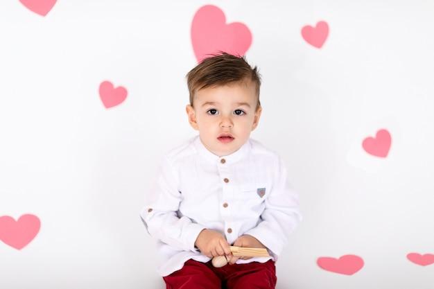Маленький младенец мальчик в белой рубашке и красные штаны на белом полу с розовыми сердечками на день святого валентина