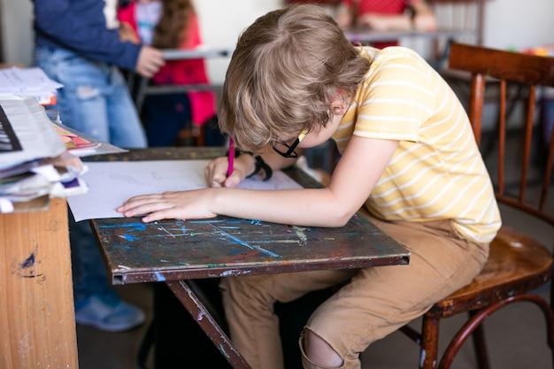 スケッチペンと教室の机で紙でかわいい男の子の肖像画。