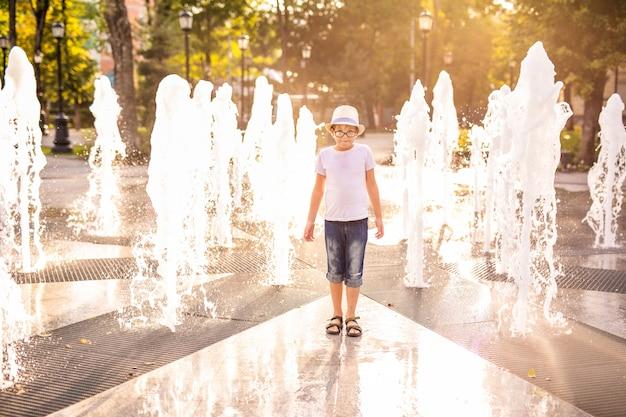 遊んで、日当たりの良い夏の公園の噴水の水を楽しんで帽子の白人少年