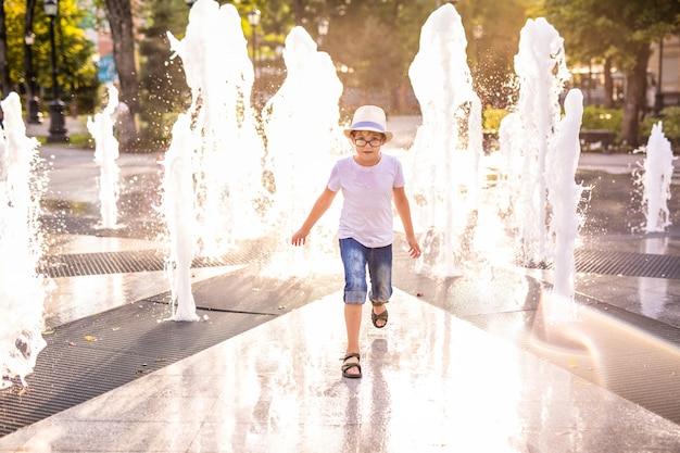 Маленький кавказский мальчик в шляпе, играть и веселиться с водой в фонтане в солнечный летний парк