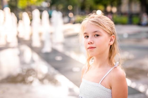 日当たりの良い夏の公園の噴水の水で遊んで、楽しんで光ドレスの白人金髪少女。