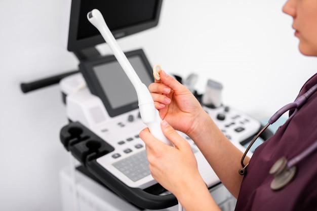 Ультразвуковой специальный датчик современного ультразвукового сканера для интравагинального обследования и небольшого медицинского презерватива для него в руках молодой женщины-врача, готовящегося к сканированию устройства. концепция здравоохранения