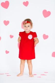 バレンタインデーにピンクのハートと白の心と赤い花輪を持つ赤いドレスの小さなブロンドの女の子