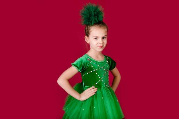 赤い壁に分離された豪華な緑のドレスで踊る美しい少女プリンセス。衣装のカーニバルパーティー