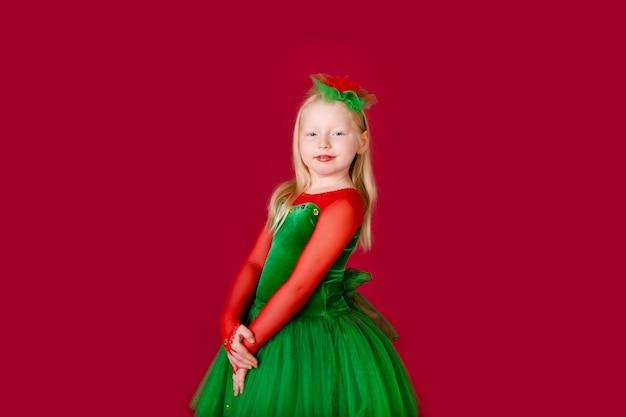 赤い壁に分離された豪華な緑のドレスで踊る美しい小さな肉付きの良い女の子の王女。衣装のカーニバルパーティー