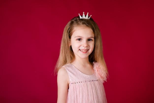 赤い壁変な顔、さまざまな感情に分離された豪華なピンクとシルバーのドレスで踊る美しい少女プリンセス