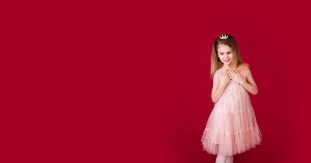 赤の背景に分離された豪華なピンクとシルバーのドレスで踊る美しい少女プリンセス。変な顔、さまざまな感情