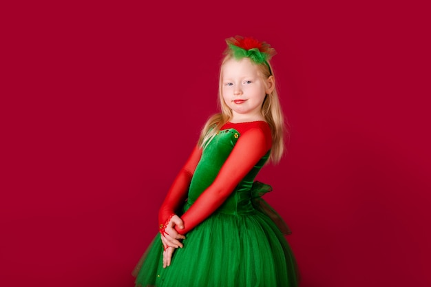 赤い壁に分離された豪華な緑のドレスで踊る美しい小さな肉付きの良い女の子の王女