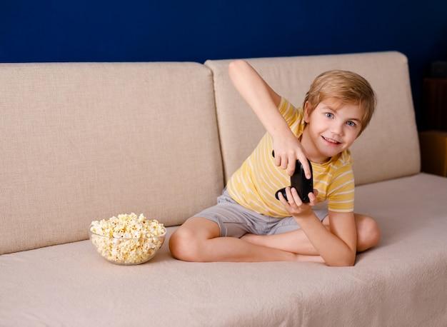 Мальчик сидит на диване, ест попкорн и играет с геймпадом во время его онлайн-урока дома, социальной дистанции во время карантина, самоизоляции, онлайн-концепции образования