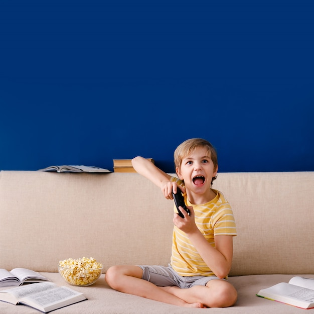 少年はソファに座って、ポップコーンを食べて、自宅で彼のオンラインレッスン中にゲームパッドで遊んで、検疫、自己分離、オンライン教育の概念の間に社会的距離