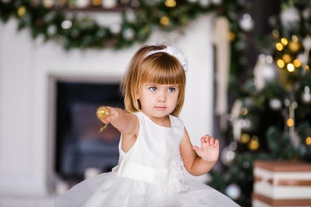 クリスマスツリーの近くの素敵なリースと白いドレスでかわいい女の子