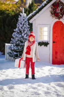 Милый маленький мальчик в красной шапке и зеленых очках находит большой подарок возле елки