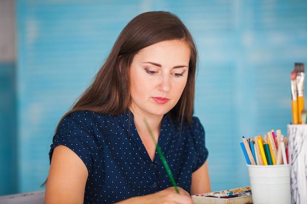 若い女性は水彩絵の具で絵を描く