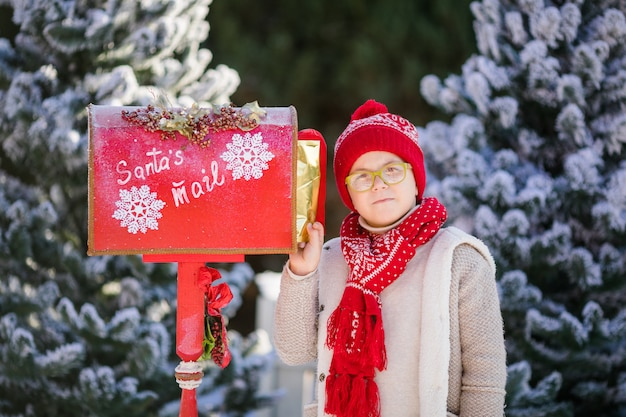 サンタのメールボックスの近くの彼の手紙と赤い帽子と緑の眼鏡の小さな男の子の笑顔