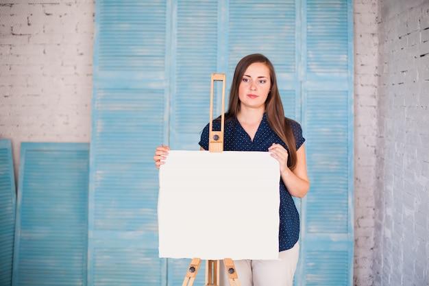 彼女のスタジオで白いキャンバスを持つアーティスト