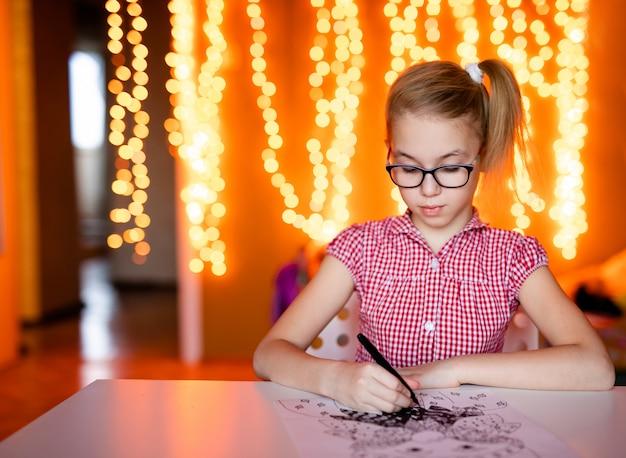 ピンクのドレスとサンタクロースを描く大きな黒いメガネでブロンドの女の子