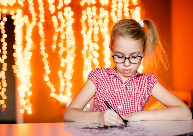 ピンクのドレスとサンタクロースを描く大きな黒いメガネでブロンドの女の子。新年のテーマ