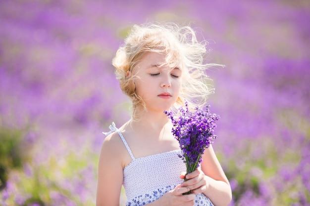 彼女の手に小さなブーケとラベンダー畑の色のドレスのブロンドの女の子