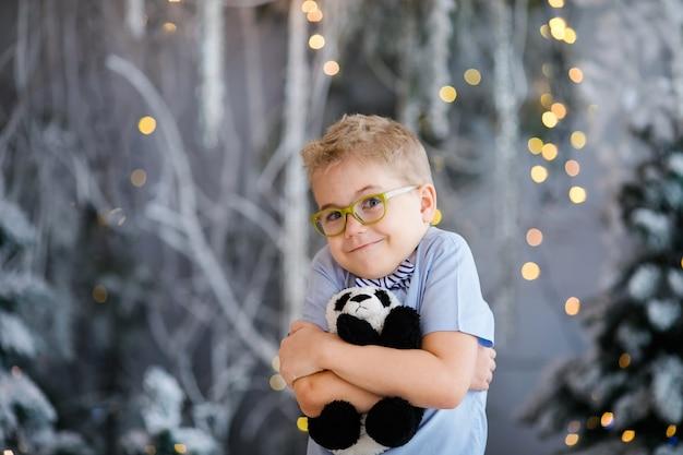 Портрет рождества счастливого мальчика ребенка с большими стеклами держа игрушку носит крытую студию