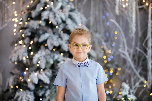 Портрет счастливого ребенка мальчика с большими очками в помещении студии