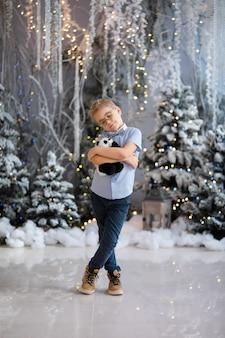 Портрет счастливого ребенка мальчик с большими очками держит игрушку медведя в помещении студии