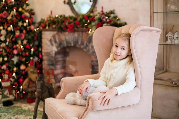 Портрет счастливой блондинки ребенка девочка в белом свитере, размещения на полу возле елки