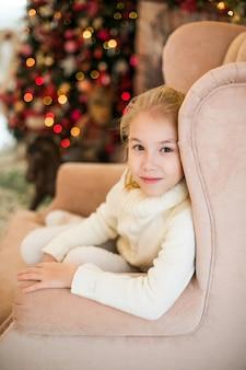 Портрет рождества счастливой белокурой девушки ребенка в белом свитере распологая на пол