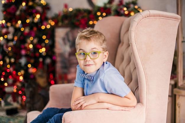 Очаровательный маленький белокурый мальчик в синей рубашке с большими очками сидит на кресле