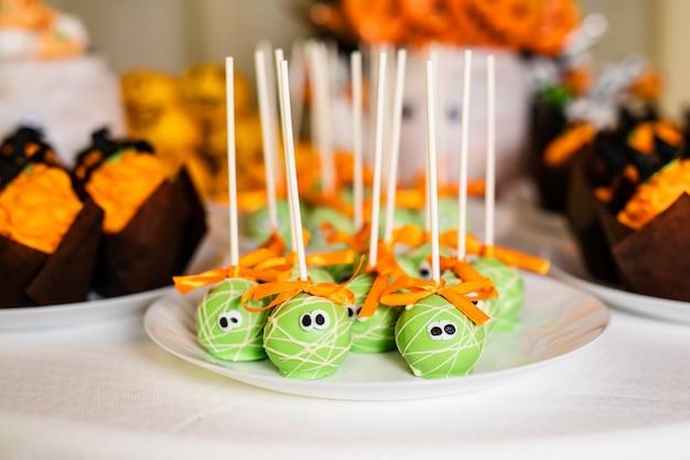 ハロウィーンのお祝いのためのキャンディーバーの上の緑のポップケーキ