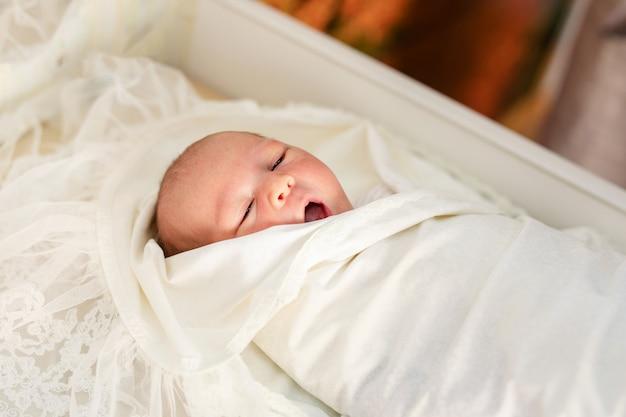 配達後の病院で彼のベビーコートで生まれたばかりの赤ちゃん。