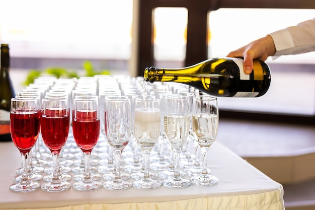 ウェイターは、路上で結婚式のケータリングでグラスにシャンパンを注ぐ