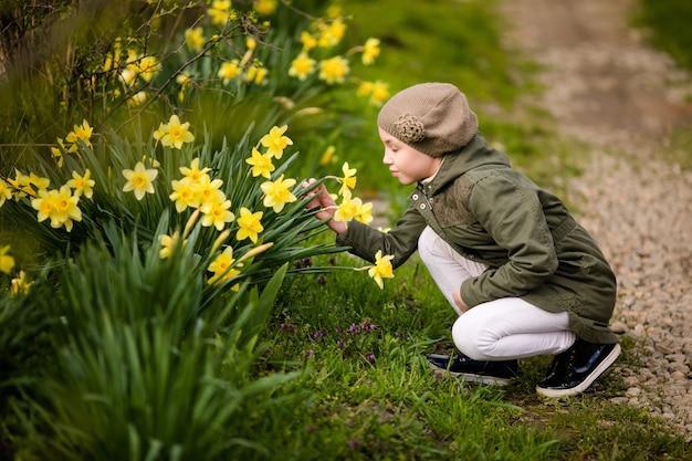 黄色の水仙の臭いがする春の国でかわいい幸せな女の子