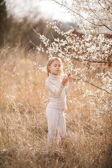 さくらの白い花の近くの花の庭で目を閉じて夢を見ているブロンドの女の子。春の桜と暖かい日当たりの良いテーマ