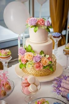 Большой сладкий многоуровневый свадебный торт, украшенный цветами