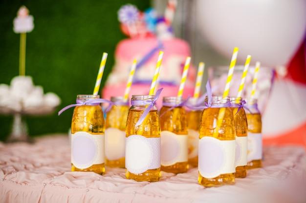 たくさんのリンゴジュース、その上の特別なラベル、白と黄色のストロー、大きなピンクのケーキ、そして白と紫の風船