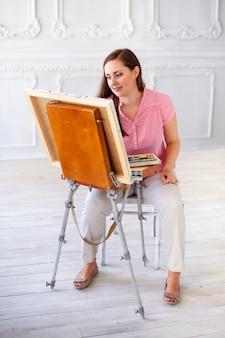 ブラシとペイントパレットを持つ女性アーティスト