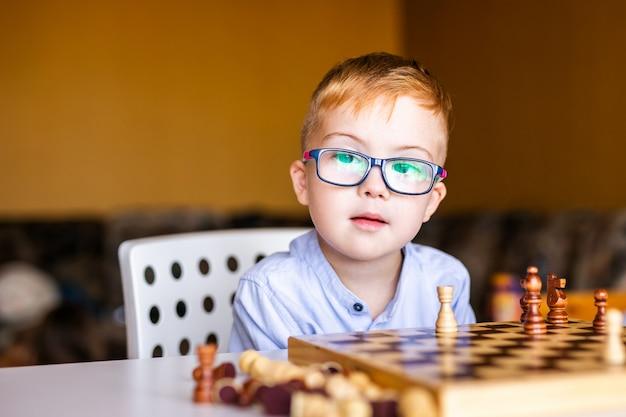 Мальчик с синдромом дауна с большими очками играет в шахматы
