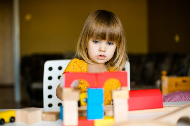 Милая маленькая девочка в желтом платье играет с разноцветными кирпичами