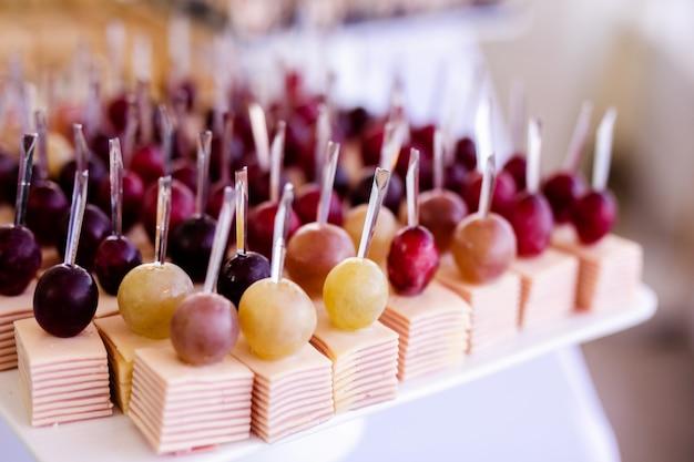 Легкие закуски в тарелке на фуршете. ассорти мини канапе, деликатесы и закуски, ресторанная еда на мероприятии. красный виноград, сыр и ветчина