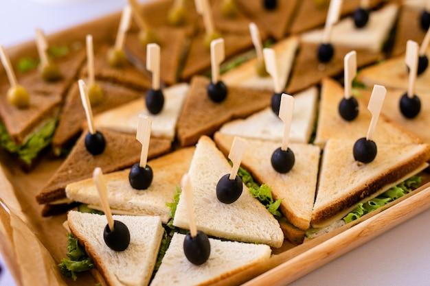 クラブサンドイッチのクローズアップ写真。生ハム、生ハム、サラダ、野菜、レタス、オリーブをスライスしたライ麦パンのサンドイッチ
