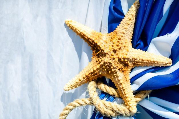 青と白のカーテンで乾燥したヒトデ。海のパーティーの装飾。
